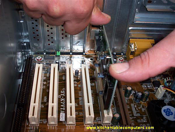 Expansion card being pressed down vertically into its slot on a motherboard