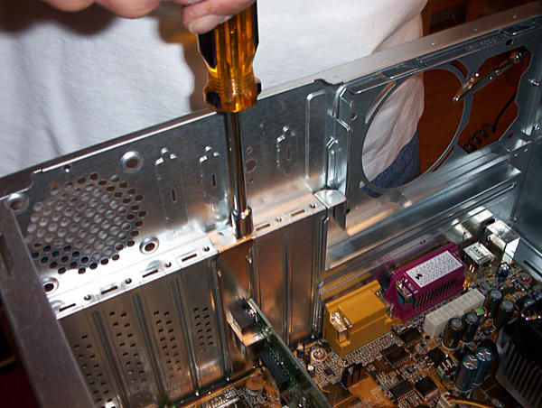 Expansion card being secured into the computer case with a screwdriver